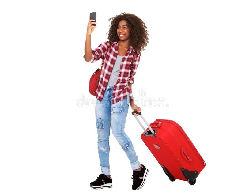 Attraktiv ung afrikansk amerikanflicka för full kropp som går med resväskan och tar selfie royaltyfri foto