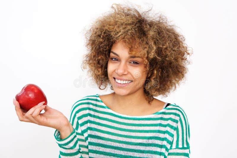 Attraktiv ung afrikansk amerikankvinna som rymmer ett äpple arkivfoto