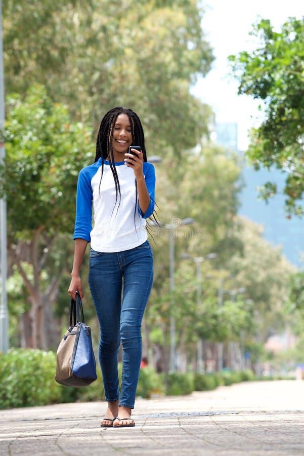 Attraktiv ung afrikansk kvinna för full kropp som utomhus går i staden genom att använda mobiltelefonen arkivbilder