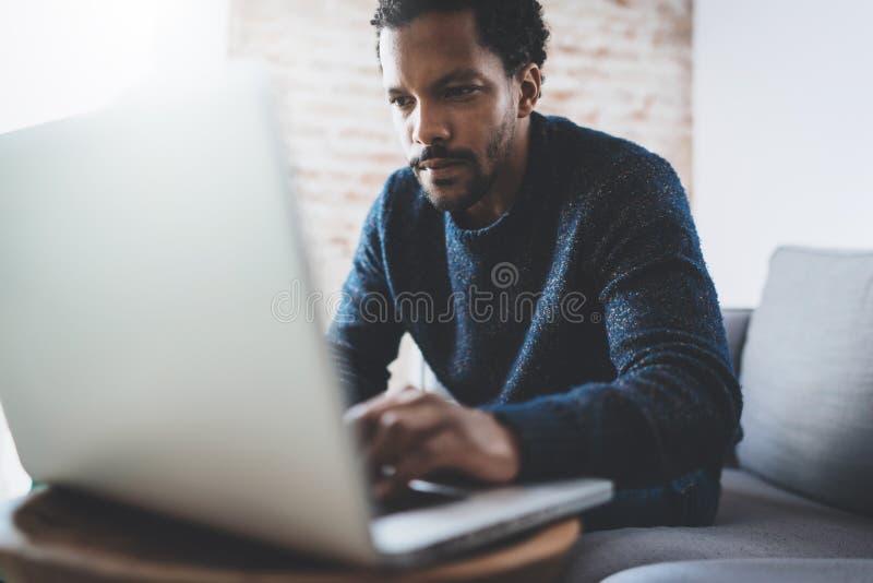 Attraktiv ung afrikansk man som använder bärbara datorn, medan sitta på hans moderna coworking ställe Begrepp av affärsfolk mycke arkivbilder