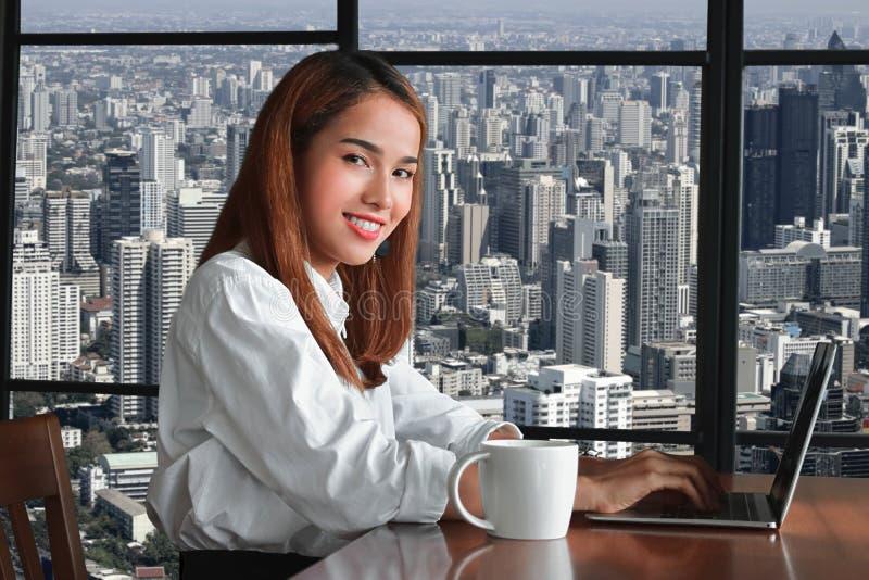 Attraktiv ung asiatisk affärskvinna med bärbara datorn som arbetar i arbetsplats av kontoret royaltyfri bild