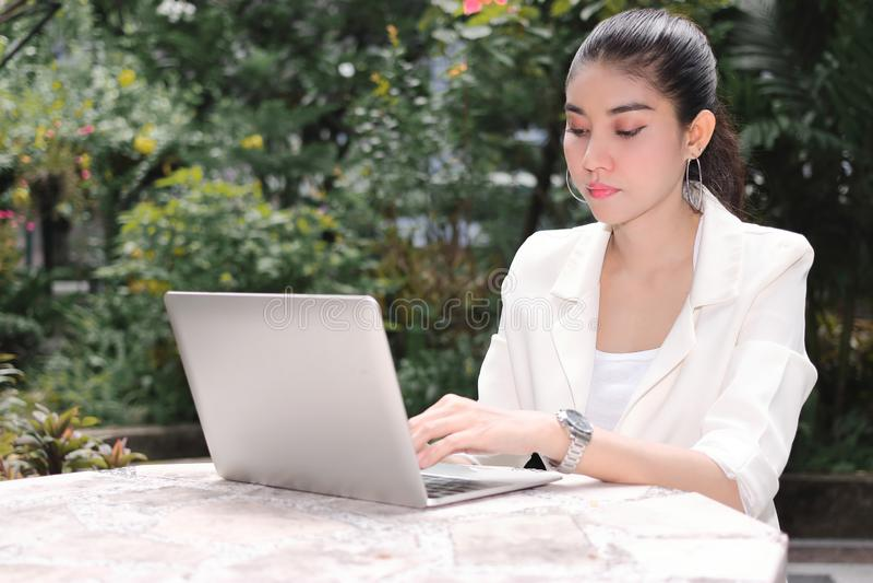 Attraktiv ung asiatisk affärskvinna som arbetar med bärbara datorn och den mobila smarta telefonen på det utvändiga kontoret arkivbilder