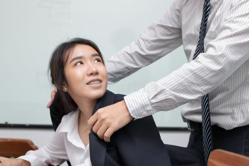 Attraktiv ung asiatisk affärskvinna som i regeringsställning ser den försiktiga mannen royaltyfri foto