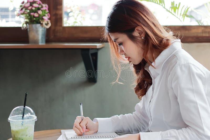 Attraktiv ung asiatisk anmärkning för handstil för affärskvinna på skrivbordet i regeringsställning royaltyfri bild