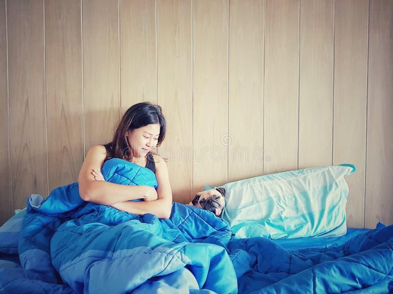 Attraktiv ung asiatisk flicka med den gulliga mopshunden, medan lägga på en säng royaltyfri foto