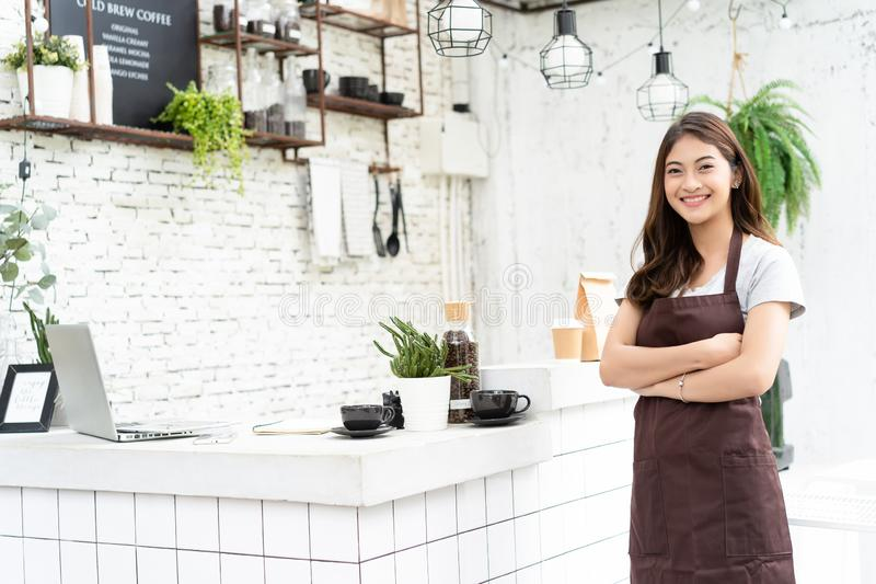 Attraktiv ung asiatisk härlig caucasian barista i förklädet som ler på kameran i coffee shopräknare startup f?retags?gare royaltyfria bilder