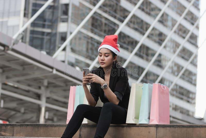 Attraktiv ung asiatisk kvinna med den santa hatten och den färgrika shoppingpåsen genom att använda den smarta telefonen för mobi arkivfoto