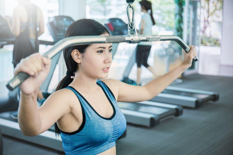 Attraktiv ung asiatisk kvinna som utarbetar med övningsmaskinen på idrottshallen royaltyfria bilder