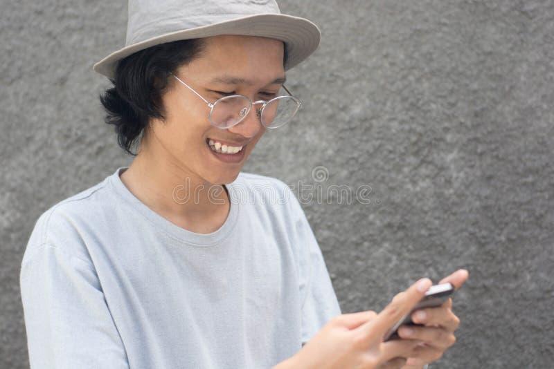 Attraktiv ung asiatisk man med hatten och exponeringsglas genom att använda smarphone och att le fotografering för bildbyråer