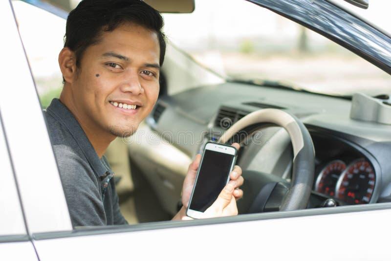 Attraktiv ung asiatisk man som ler och ser kameran, medan visa hans smartphone till kameran royaltyfria bilder