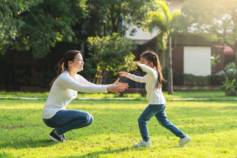 Attraktiv ung asiatisk moder och liten gullig flickadotterkörning som kramar hennes mamma i trädgård efter tillbaka skola i afton royaltyfria foton