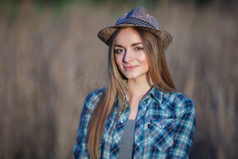 Attraktiv ung blond kvinna i blå hatt för sugrör för plädskjorta som utomhus tycker om hennes tid på äng arkivfoton