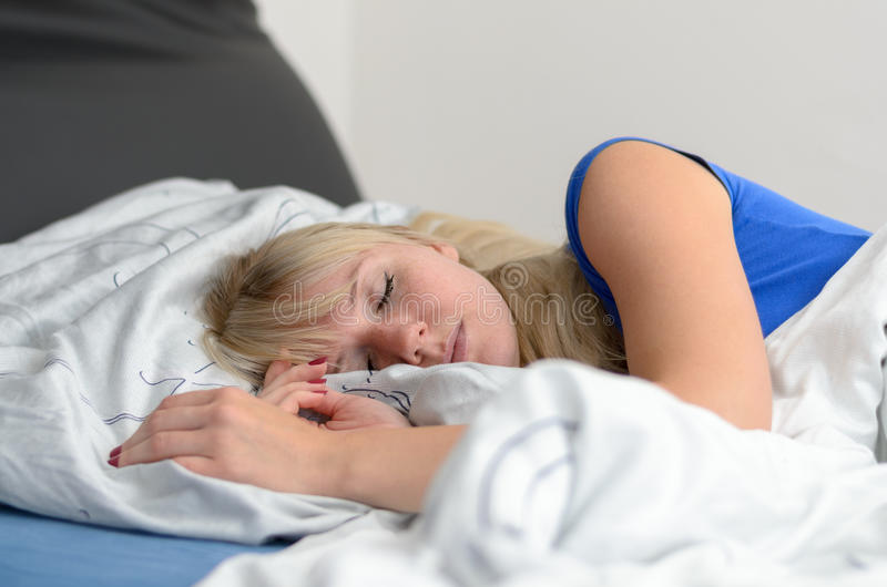 Attraktiv ung blond kvinna som sover i hennes säng royaltyfri foto