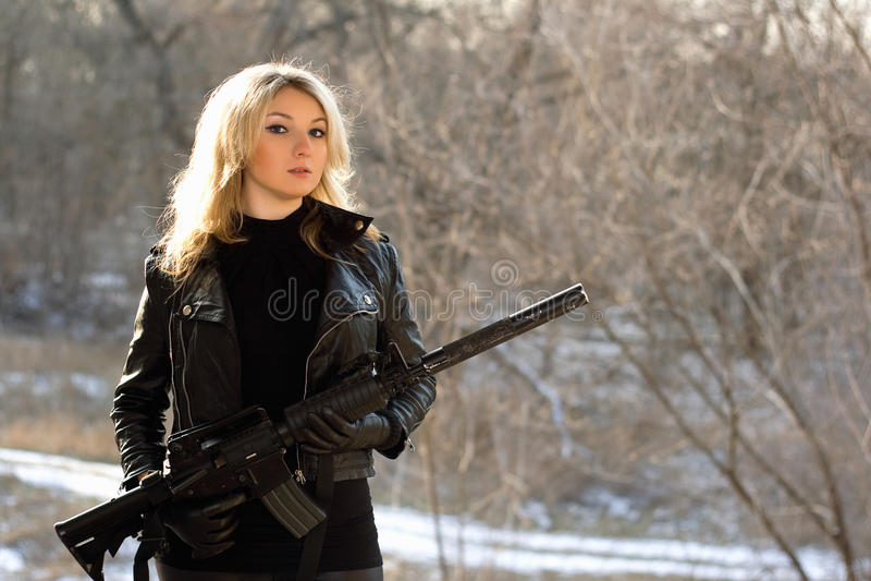Attraktiv ung blondin med ett vapen fotografering för bildbyråer
