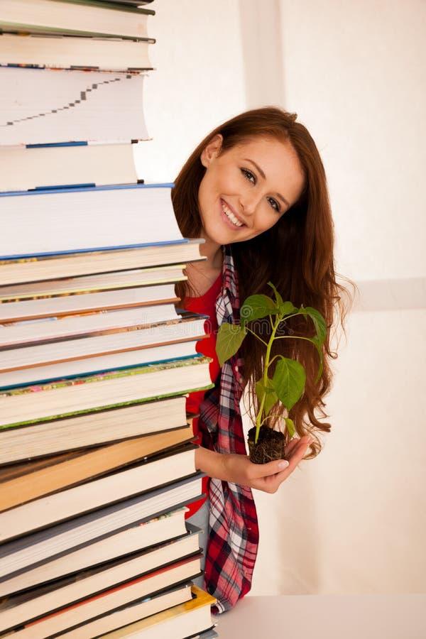 Attraktiv ung botanikstudent med seedlnng och böcker royaltyfria bilder