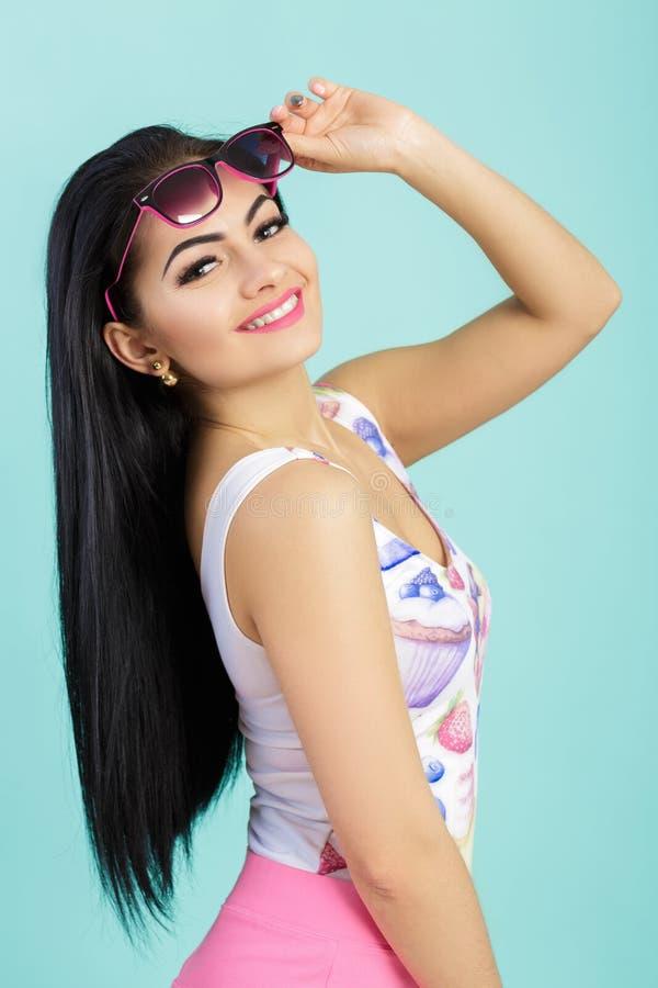 Attraktiv ung brunettkvinna i rosa ärmlös tröja på blå bakgrund Smilling flicka i solglasögon fotografering för bildbyråer