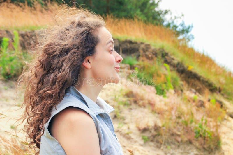 Attraktiv ung brunettkvinna med lockigt storartat hår som skrattar på naturen royaltyfri foto