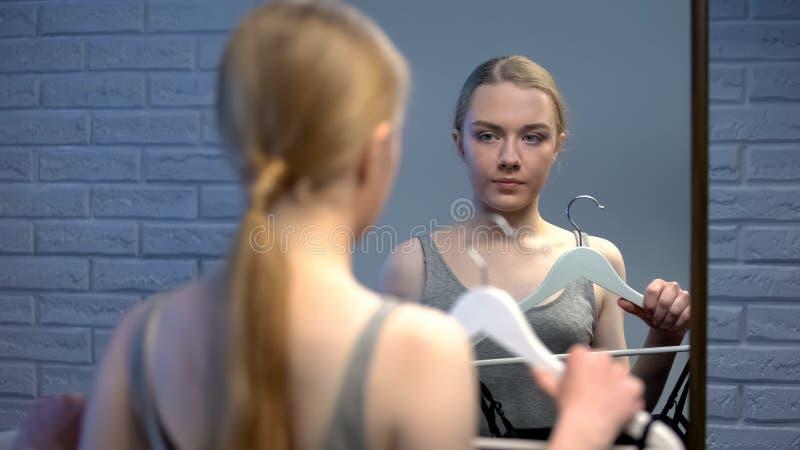 Attraktiv ung dam som väljer klänningen för partiframdel av spegeln, datumförberedelse royaltyfri foto