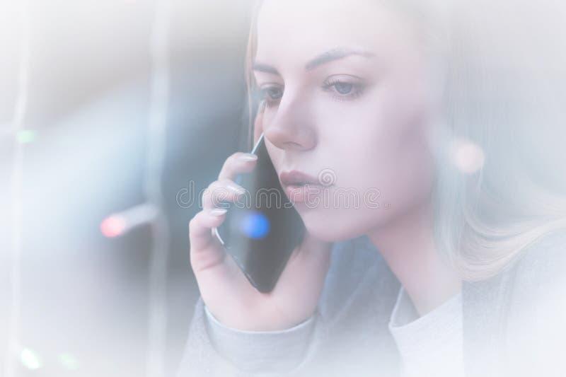 Attraktiv ung flicka för Closeupstående som talar på telefonen denkontrast sikten till och med reflexionen av ställer ut fotografering för bildbyråer