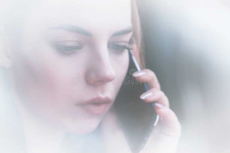 Attraktiv ung flicka för Closeupstående som talar på telefonen denkontrast sikten till och med reflexionen av ställer ut arkivfoto