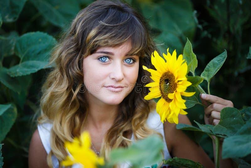 Attraktiv ung flicka i fältet av solrosor royaltyfri foto
