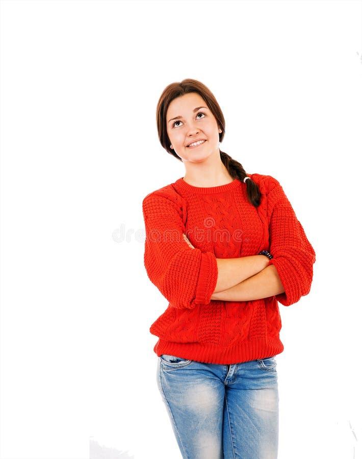 Attraktiv ung flicka i röd sweater och jeans som tänker ab arkivbild