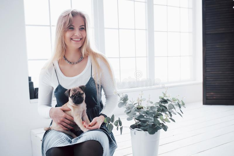Attraktiv ung flicka med den gulliga mopshunden på händerna fotografering för bildbyråer