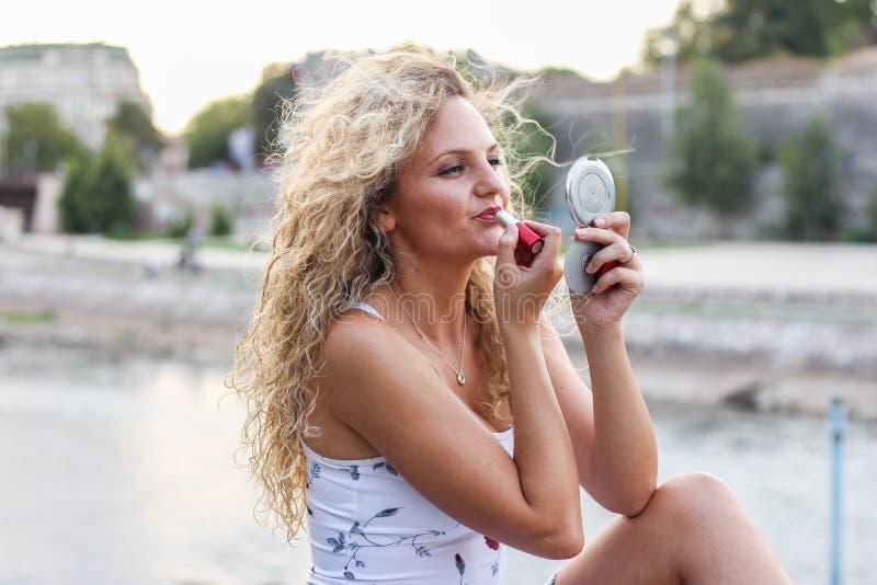 Attraktiv ung flicka med lockigt blont hår som sätter en läppstift arkivfoton