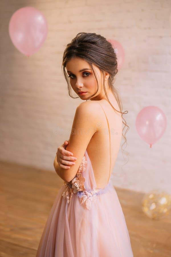 Attraktiv ung flicka med mörkt hår i en ursnygg frisyr som är iklädd en lång försiktig rosa färg med en purpurfärgad klänning med royaltyfri fotografi