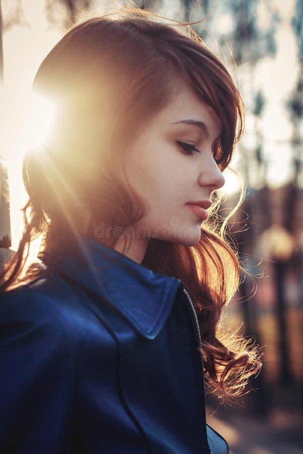 Attraktiv ung flicka på strålar för stadsgatasolnedgång fotografering för bildbyråer