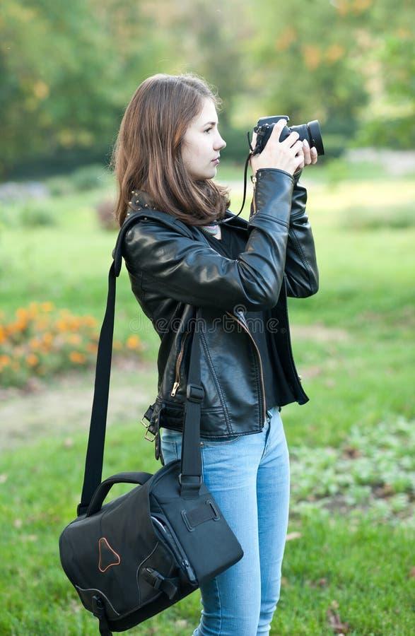 Attraktiv ung flicka som utomhus tar bilder Den gulliga tonårs- flickan i jeans och det svarta läderomslaget som tar foto parkera arkivbild
