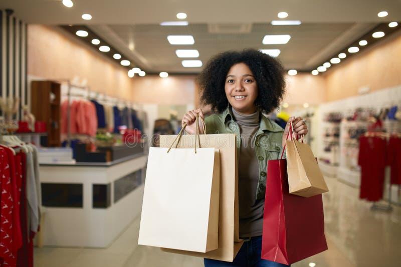Attraktiv ung gullig afrikansk amerikankvinna som poserar med shoppingpåsar med klädlagret på backgroud Nätt svart royaltyfri bild