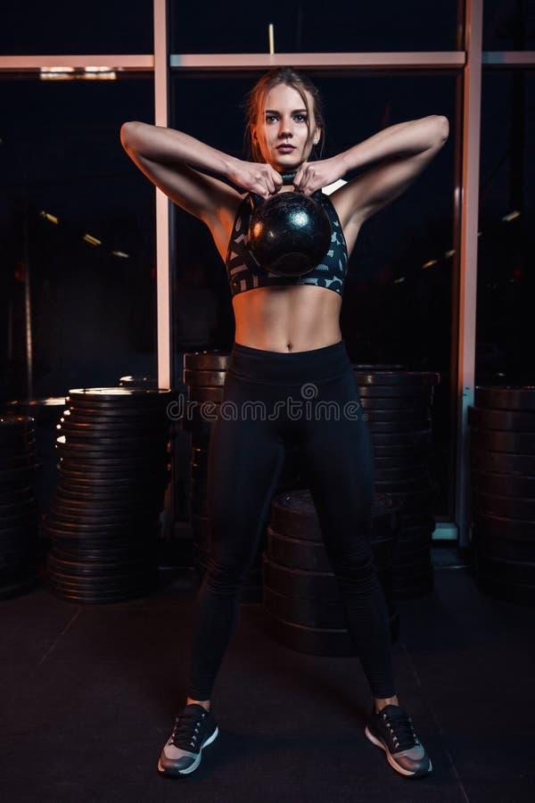 Attraktiv ung idrottsman nen med den muskulösa kroppen som övar crossfit Kvinna i sportswearen som gör crossfitgenomkörare med ko arkivbild