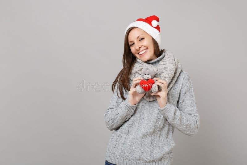 Attraktiv ung jultomtenflicka i den gråa tröjan, leksak för björn för nalle för innehav för halsdukjulhatt som flott isoleras på  arkivfoton