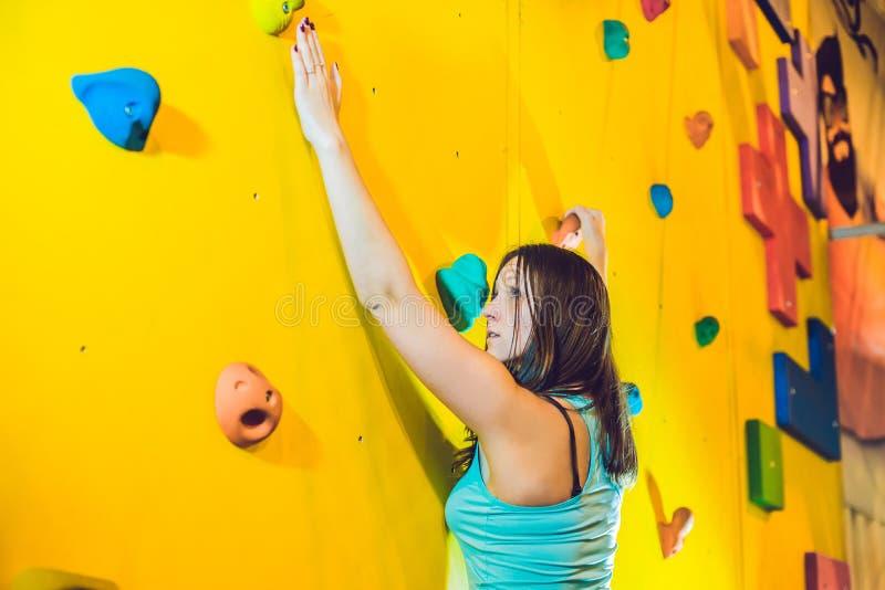 Attraktiv ung klättrarekvinna för yrkesmässig sport som har utbildning i idrottshallen på den konstgjorda väggen arkivfoton