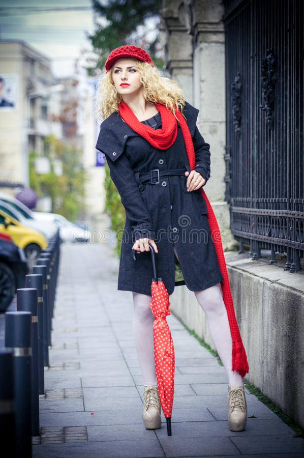 Attraktiv ung kvinna i ett vintermodeskott. Härlig ung flicka med det röda paraplyet i gatan royaltyfri bild