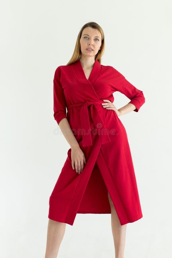 Attraktiv ung kvinna i röd klänning med handen på midjan fotografering för bildbyråer
