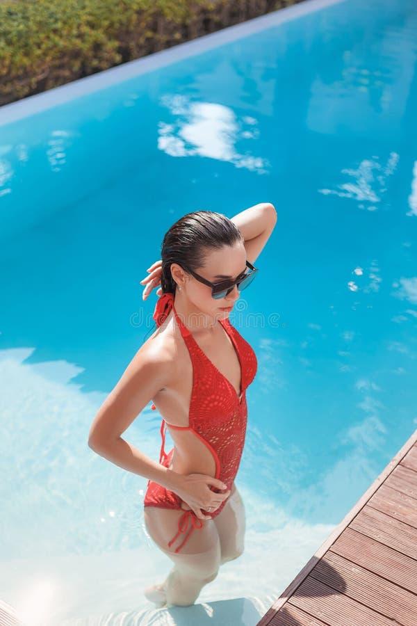 attraktiv ung kvinna i röd stilfull baddräkt fotografering för bildbyråer