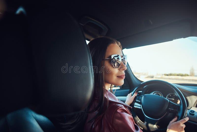 Attraktiv ung kvinna i rött omslag och solglasögon, i körning av hennes bil arkivbild
