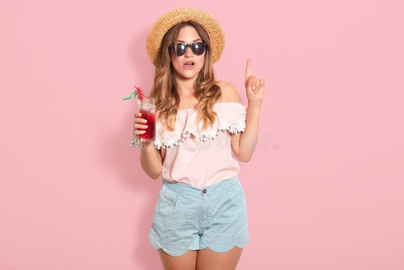 Attraktiv ung kvinna i sommardräkt på rosa bakgrund Lycklig flicka i solglasögon som poserar med den sugrörhatten och coctailen, arkivbilder