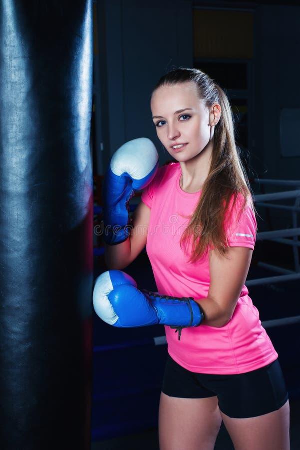 Attraktiv ung kvinna med blåa boxninghandskar i sportidrottshall Härlig kvinnlig boxare med att stansa påsen arkivfoto