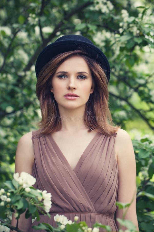 Attraktiv ung kvinna med brunt hår och naturlig makeup på livsstil för för för blommabakgrundsdet fria, mjukhet och softness royaltyfri fotografi