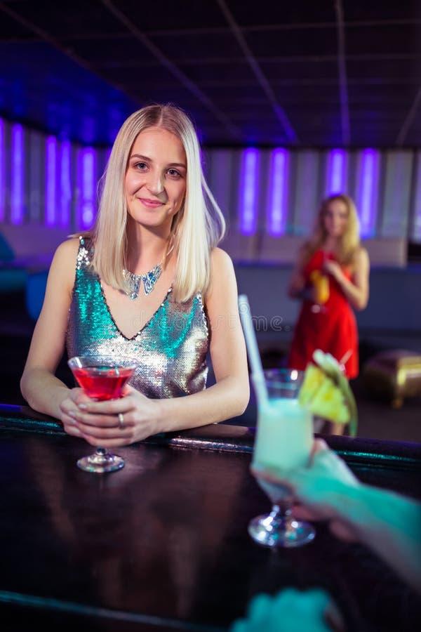 Attraktiv ung kvinna med coctailen i nattklubb arkivbild