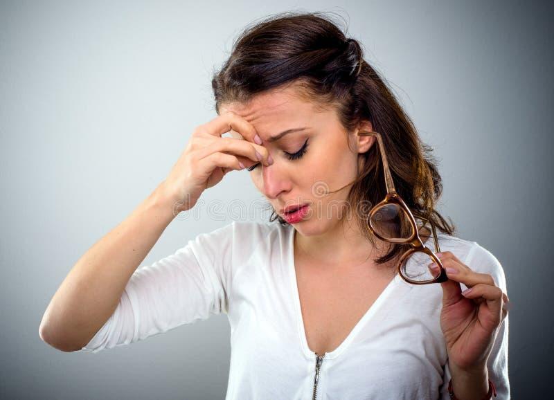 Attraktiv ung kvinna med en huvudvärk royaltyfri foto