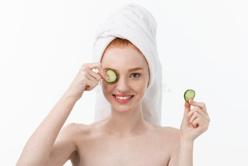 Attraktiv ung kvinna med härlig ren hud Vita maskering och gurkor Skönhetbehandling- och cosmetologybrunnsort royaltyfri fotografi
