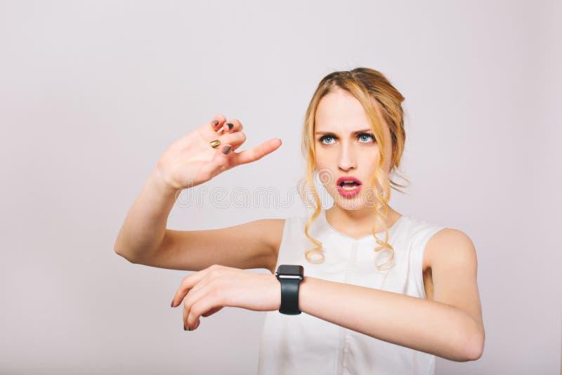 Attraktiv ung kvinna med lockigt hår som bär stilfulla blusblickar på den svarta armbandsur- och plandagen Charmig blondin arkivfoto