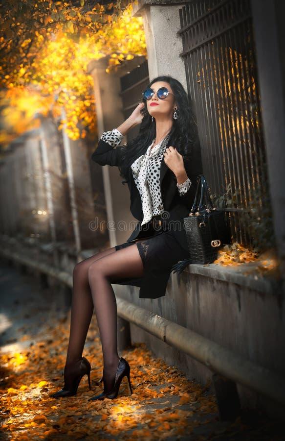 Attraktiv ung kvinna med solglasögon i höstligt modeskott Härlig dam i svartvit dräkt med sammanträde för kort kjol royaltyfria bilder