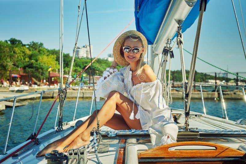 Attraktiv ung kvinna på en yacht på en sommardag arkivfoton
