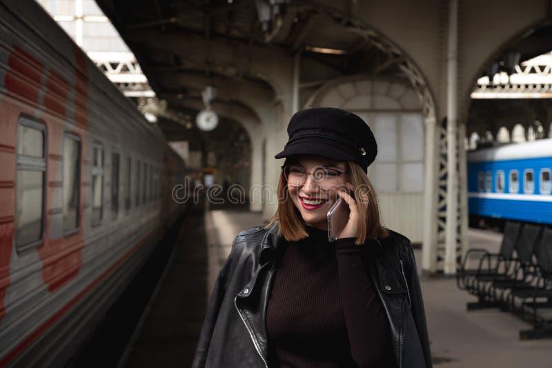 Attraktiv ung kvinna som är millenial i svart kläder och en hatt på järnvägsstationen bredvid drevet Talar på en mobil arkivbilder
