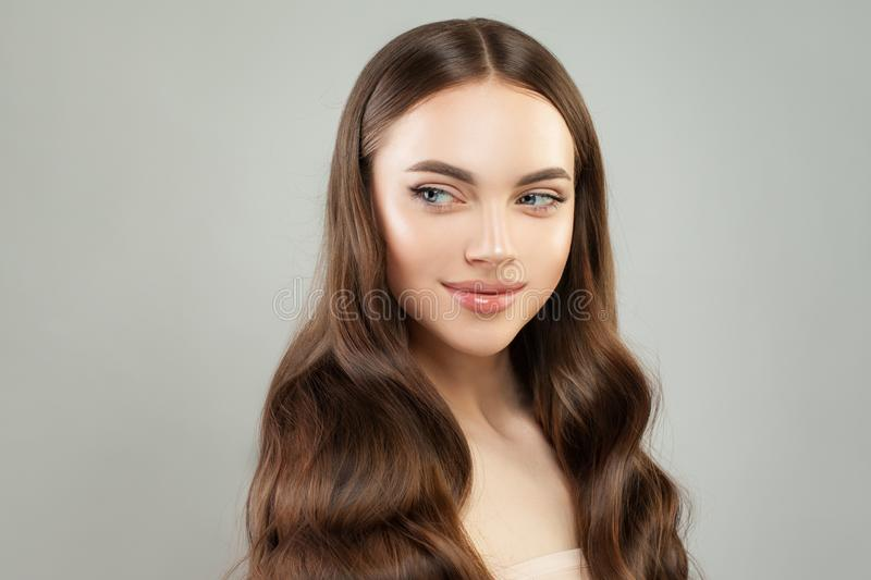 Attraktiv ung kvinna som åt sidan ler och ser Flicka med klar hud och perfekt hår royaltyfri bild